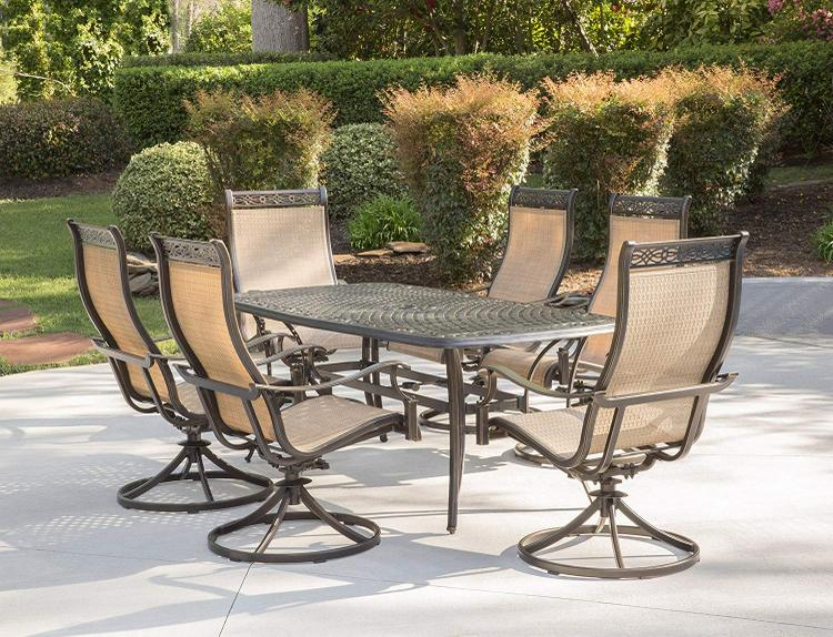 Hanover Manor 7-Piece Outdoor Dining Set with 6 Swivel Rockers, a 60 In. Cast-top Dining Table, and a 9 Ft. Table Umbrella with Stand